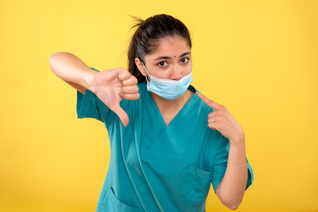 黄色の壁にthumdownサインを作る医療マスクを持つ若い女性の正面図