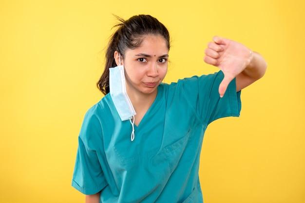 黄色の壁に親指ダウンサインを作る医療マスクを持つ若い女性の正面図