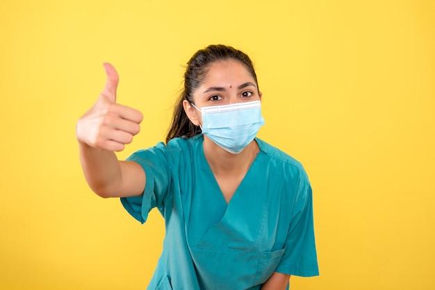 노란색 벽에 가입 엄지 손가락을 만드는 의료 마스크와 젊은 여성의 전면보기