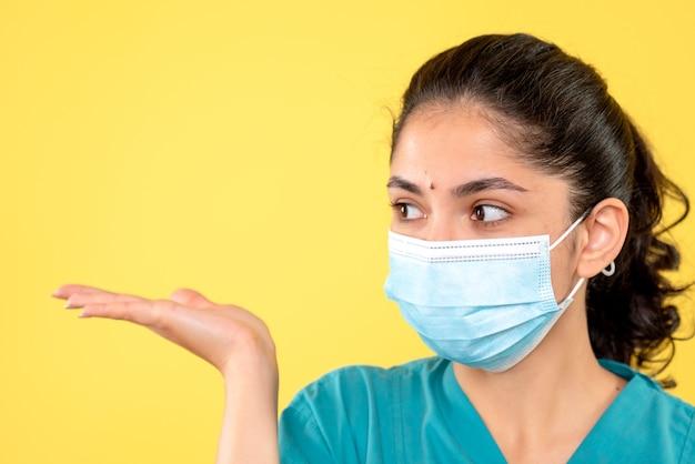 黄色の隔離された壁に医療マスクを持つ若い女性の正面図