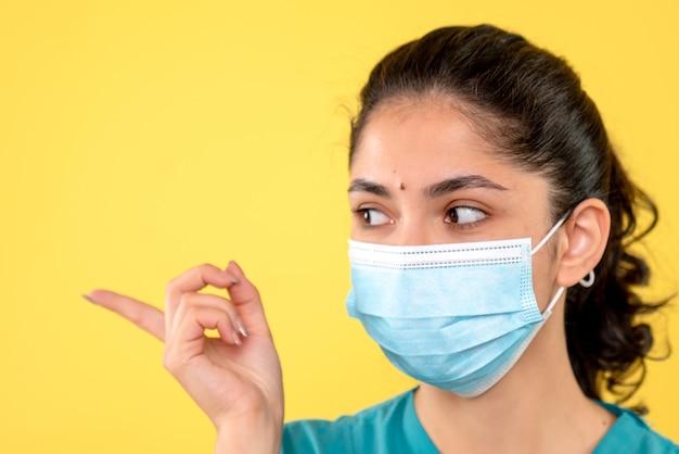 노란색 벽에 의료 마스크와 젊은 여성의 전면보기