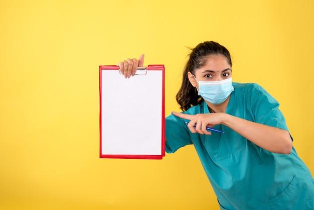 Вид спереди молодой женщины с медицинской маской, указывающей на буфер обмена на желтой стене
