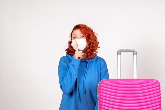 白い壁にマスクでピンクのバッグを持つ若い女性の正面図