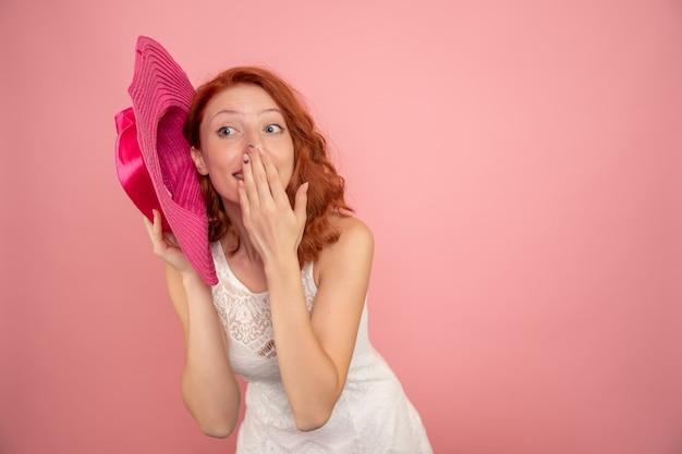 분홍색 벽에 분홍색 모자와 젊은 여성의 전면보기