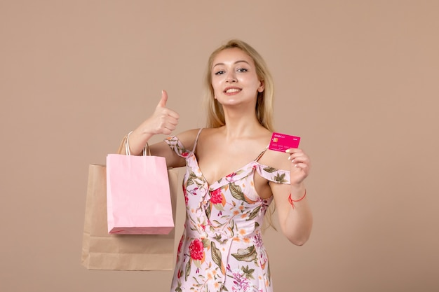 茶色の壁に買い物袋と銀行カードを持つ若い女性の正面図