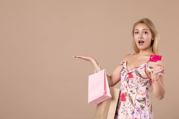 갈색 벽에 쇼핑백과 은행 카드를 든 젊은 여성의 전면 모습