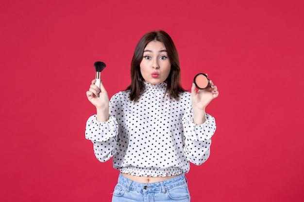 赤い壁に化粧をしているタッセルとパウダーを持つ若い女性の正面図