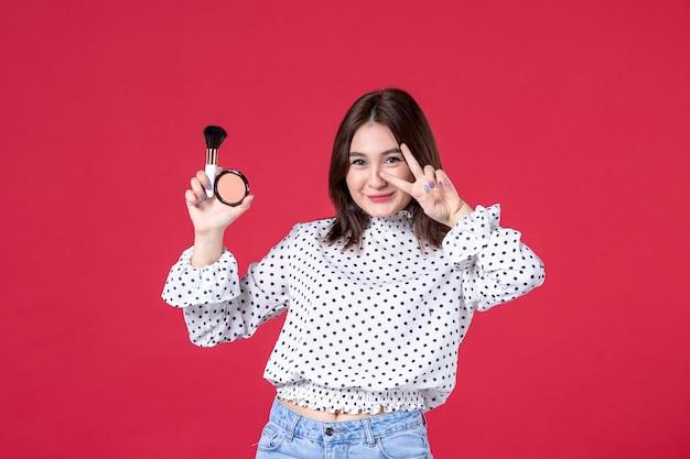 赤い壁に化粧のためのタッセルとパウダーと若い女性の正面図