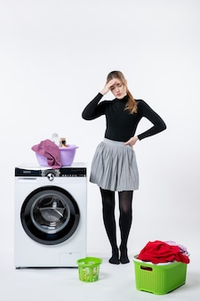Вид спереди молодой женщины со стиральной машиной и грязной одеждой с головной болью на белой стене
