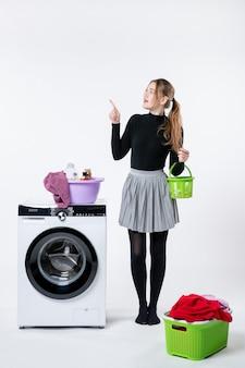 Вид спереди молодой женщины со стиральной машиной и грязной одеждой на белой стене