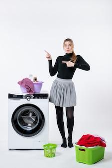 흰 벽에 세탁기와 더러운 옷을 입은 젊은 여성의 전면