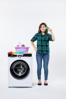 白い壁に緑の銀行カードを保持している洗濯機を持つ若い女性の正面図