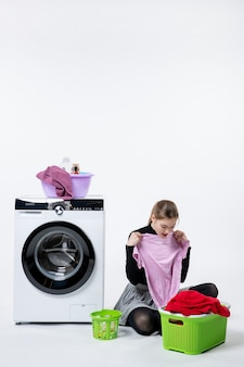 흰색 벽에 세탁기와 더러운 옷을 입은 전면 보기 젊은 여성