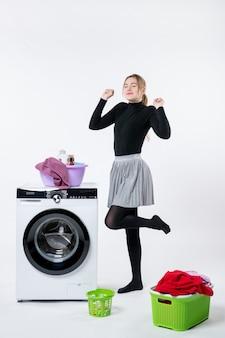 白い壁に洗濯機と汚れた服を着た若い女性の正面図