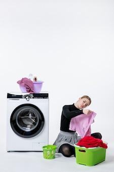 Вид спереди молодая женщина со стиральной машиной и грязной одеждой на белой стене