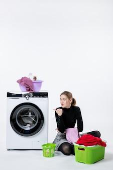 Вид спереди молодой женщины со стиральной машиной, складывающей грязную одежду на белой стене