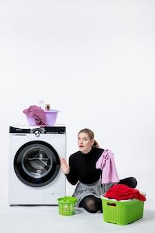 흰 벽에 더러운 옷을 접는 세탁기를 가진 젊은 여성의 전면