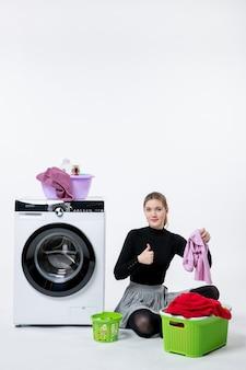 白い壁に汚れた服を折りたたむ洗濯機を持つ若い女性の正面図