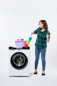 Вид спереди молодой женщины со стиральной машиной, держащей пылесос на белой стене