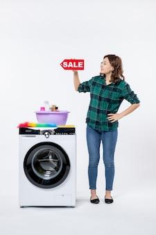 흰색 벽에 판매 배너를 들고 세탁기와 젊은 여성의 전면 보기