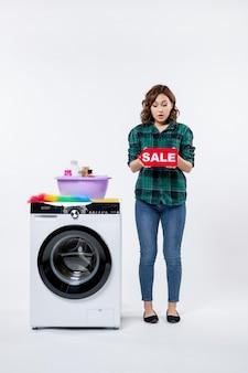 白い壁に販売書き込みを保持している洗濯機を持つ若い女性の正面図