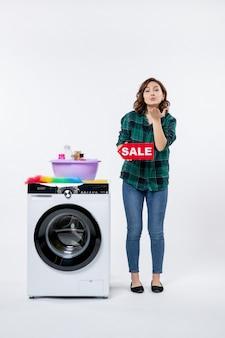 Вид спереди молодой женщины со стиральной машиной, держащей распродажу на белой стене