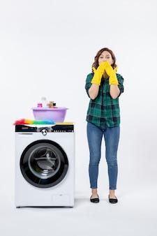 Вид спереди молодой женщины со стиральной машиной в желтых перчатках на белой стене