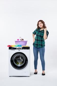 白い壁に洗濯機と若い女性の正面図