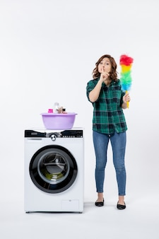 흰 벽에 세탁기가 있는 젊은 여성의 전면 모습