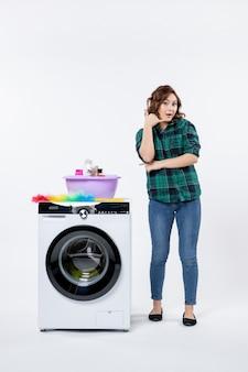 Вид спереди молодой женщины со стиральной машиной на белой стене