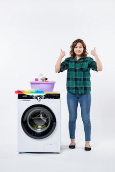 흰 벽에 세탁기를 들고 있는 젊은 여성의 전면 모습