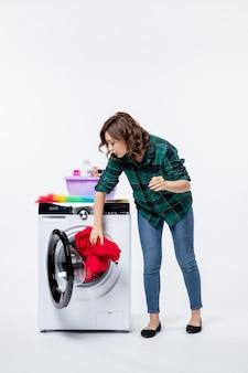 白い壁に洗濯物を洗うために洗濯機を準備している若い女性の正面図