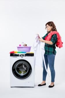 흰 벽에 세탁할 옷을 준비하는 세탁기를 가진 젊은 여성의 전면 무료 사진
