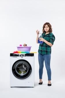 흰 벽에 액체 가루를 준비하는 세탁기를 가진 젊은 여성의 전면
