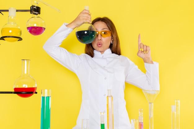 Вид спереди молодой женский химик в белом костюме перед столом, работающих с решениями