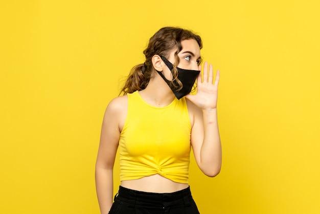 Вид спереди молодой девушки, зовущей кого-то на желтой стене