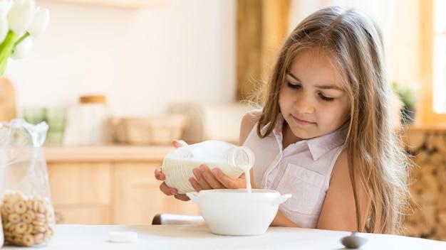 朝食にシリアルを食べる少女の正面図