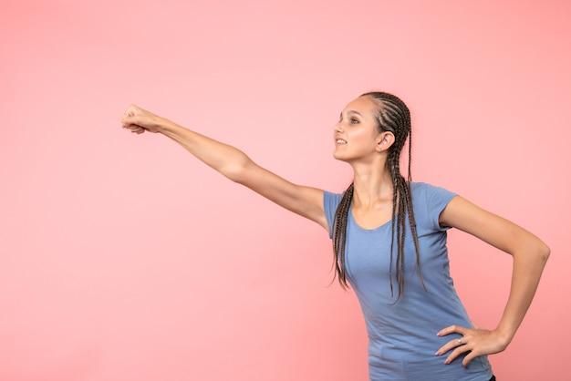 Вид спереди молодой девушки в позе супермена на розовом
