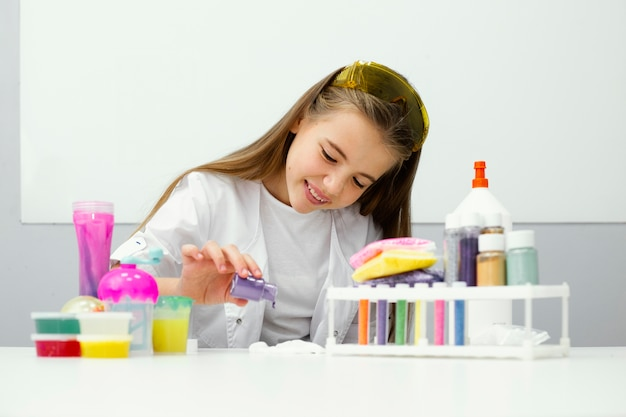 점액과 색상을 실험하는 어린 소녀 과학자의 전면보기