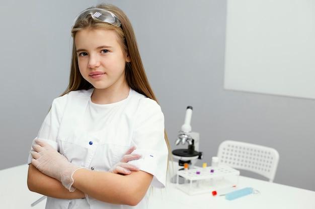 실험실 코트에서 포즈를 취하는 어린 소녀 과학자의 전면보기