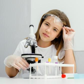 현미경을 사용하는 동안 포즈를 취하는 어린 소녀 과학자의 전면보기