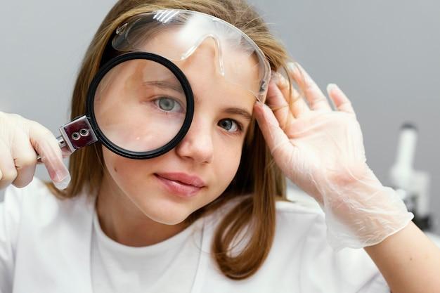 돋보기와 어린 소녀 과학자의 전면보기