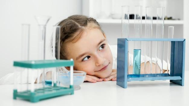 실험실에서 테스트 튜브와 어린 소녀 과학자의 전면보기
