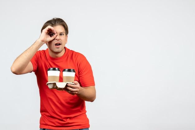 白い背景の上の眼鏡ジェスチャーを作る紙コップでコーヒーを保持している赤いブラウスの若い男の正面図