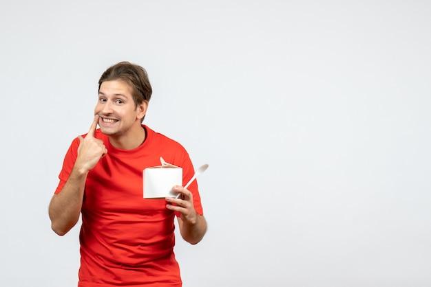 白い背景の上の沈黙のジェスチャーを作る紙箱とスプーンを保持している赤いブラウスの若い男の正面図