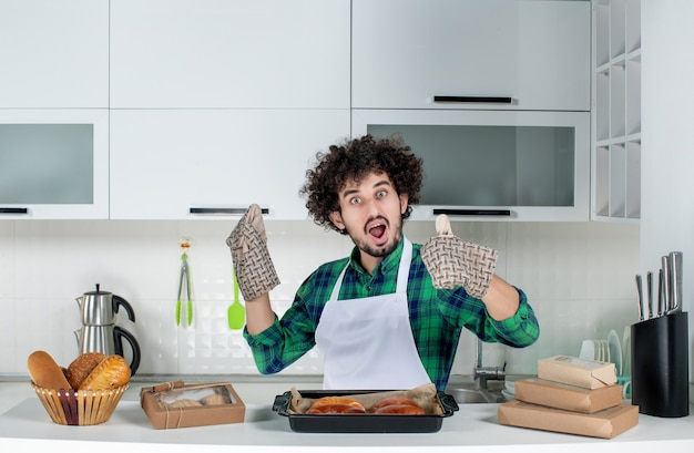 Вид спереди молодого парня в держателе, стоящего за столом со свежеиспеченной выпечкой, делая жест на белой кухне