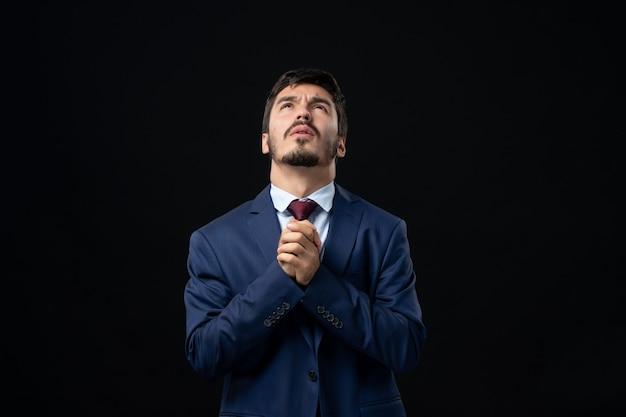 Вид спереди молодого обнадеживающего бородатого мужчины, молящегося за бога на изолированной темной стене