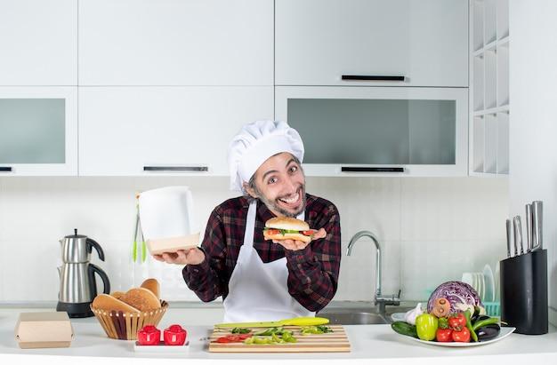 台所のテーブルの後ろに立っているハンバーガーを持ち上げて空腹の若い男の正面図