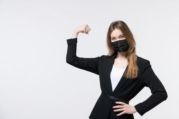 サージカルマスクを着用し、白で彼女の成功を楽しんでいるスーツを着た若い女性の正面図