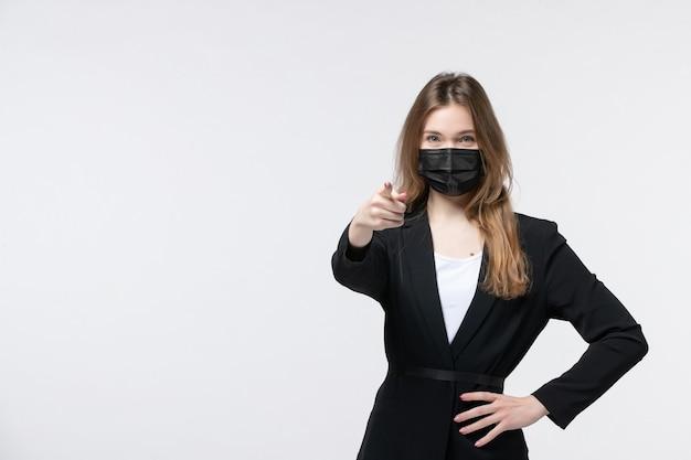サージカルマスクを着用し、白で誰かを指しているスーツを着た若い女性の正面図